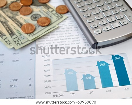 Money and calculator on the home sales chart - stock photo