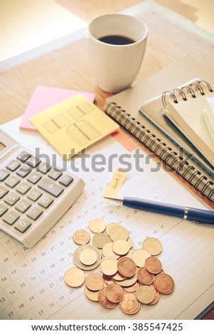 money and calculator on wooden table with vintage color concept - stock photo