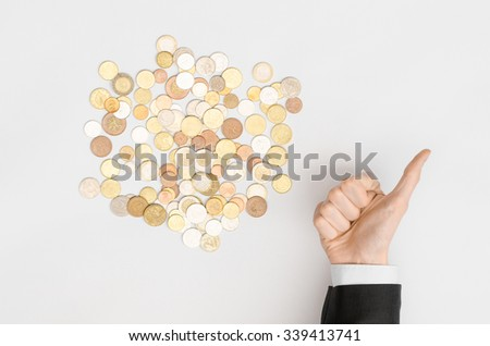 Money and Finance Topic: Money coins and human hand in black suit showing gesture on a gray background top view - stock photo