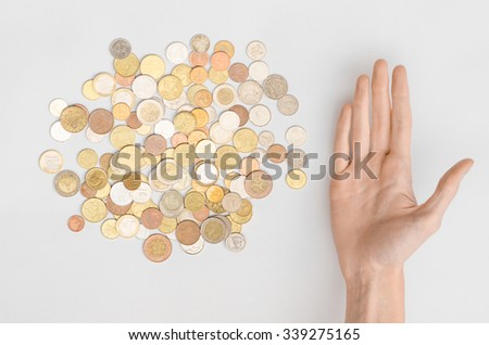 Money and Finance Topic: Money coins and human hand on a gray background in studio top view - stock photo