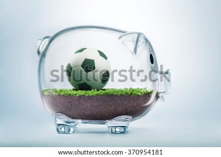 Money and football business concept with soccer ball inside transparent piggy bank - stock photo
