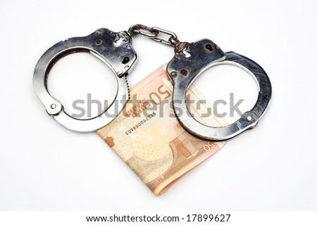 money and handcuffs over white