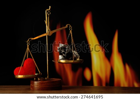 Money and heart in balance scales on dark glowing background - stock photo