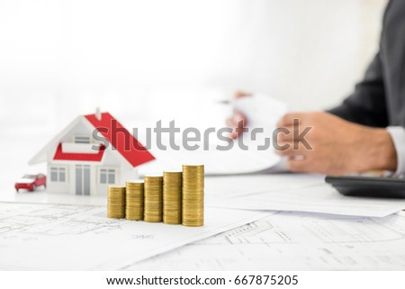 Businessman property agent investor calculating growth stock photo money and house model on blueprint paper at the table with blurred businessman in background malvernweather Image collections