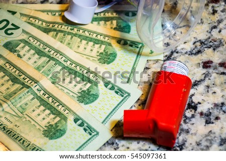 Money and Inhaler for respiratory problems the Medical Healthcare Pharmaceutical industry costs lots of money with 20 dollar bills  on counter