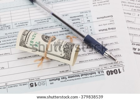 Money and pen on tax form background