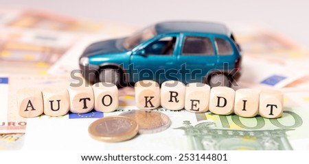 Money and wood cubes with the german words car loan / car loan - stock photo