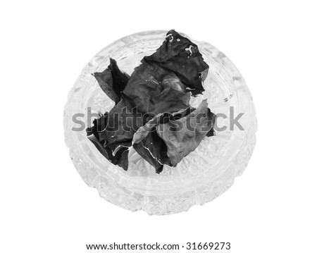 Money ashes in ashtray isolated on white