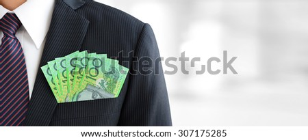 Money,Australian dollar (AUD) banknotes, in businessman suit pocket - financial and investment panoramic background with copy space - stock photo