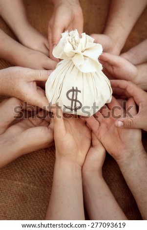 Money Bag in group hands - stock photo