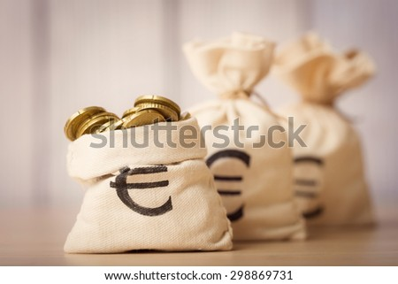 Money bags with euro coins - stock photo