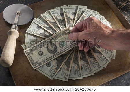 money baked into pie with pie cutter - stock photo