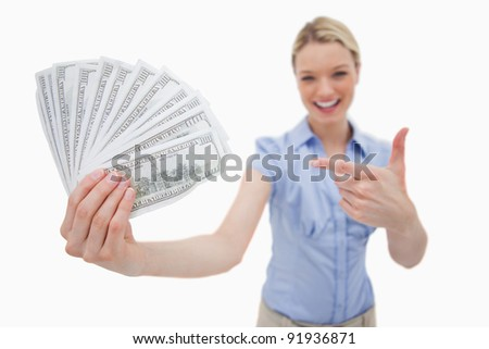 Money being held and pointed at by woman against a white background