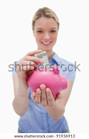Money being put into piggy bank by woman against a white background - stock photo