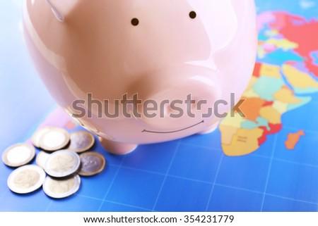 Money box pig on world map background - stock photo