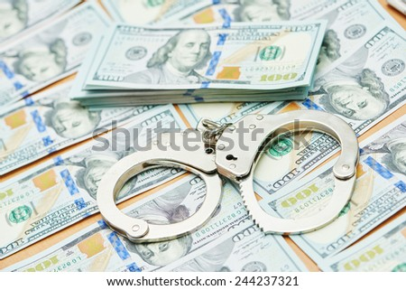 money bribe or corruption theme. handcuffs lying on dollars banknotes - stock photo