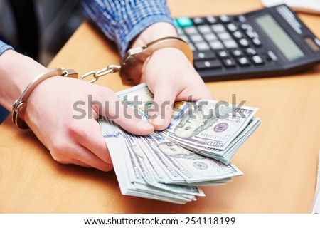 money bribe or corruption theme. male hands with dollars banknotes in handcuffs - stock photo