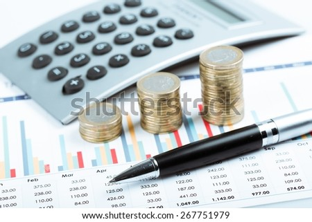 Money. Business diagram on financial report with coins and calculator - stock photo