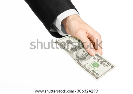 Money & Business theme: businessman's hand in a black suit holding a banknote of 100 dollars on white isolated background in studio