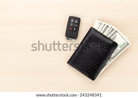 Money cash wallet and car remote key on wooden table. View from above with copy space - stock photo