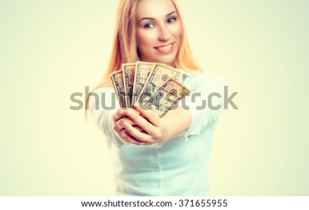 Money. Closeup portrait beautiful young pretty business woman fashion girl looking at you camera holding giving you money usd dollar currency isolated green yellow background wall. Lottery win concept - stock photo
