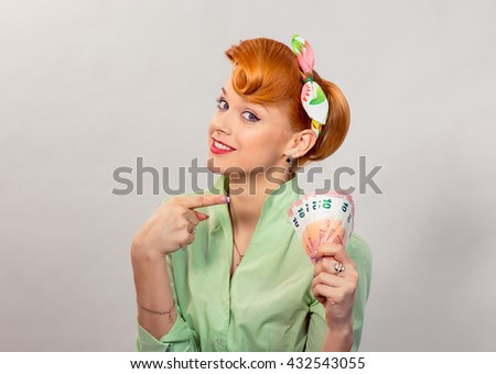 Money. Closeup portrait beautiful young pretty business woman fashion girl looking at you camera holding showing pointing money european currency isolated yellow background wall. Lottery win concept - stock photo