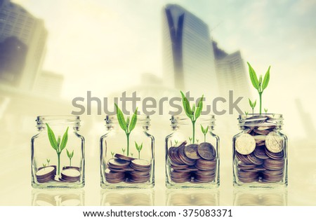 money coins and seed in clear bottle on cityscape photo blurred cityscape background,Business investment growth concept