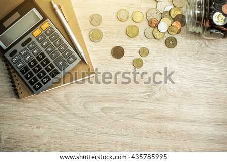 Money (coins), calculator and some stationery on wood table, top view with copy space - financial background concept - stock photo