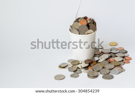 Money coins in a cup of ice cream on a white background concept Saving money - stock photo
