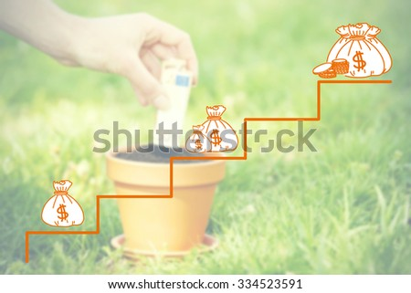 Money concept.Female hand planting money into flowerpot - stock photo