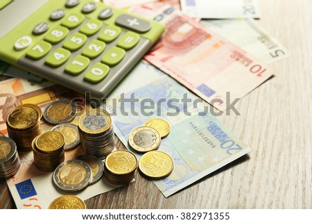 Money concept. Green calculator with banknotes and coins, close up