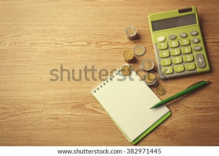 Money concept. Green calculator with coins and notebook on wooden table - stock photo