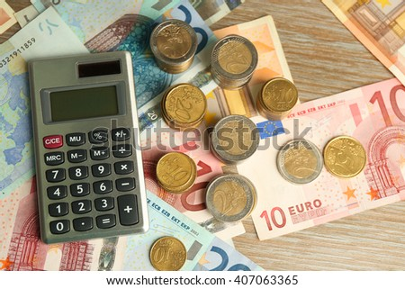 Money concept. Grey calculator with banknotes and coins, close up - stock photo