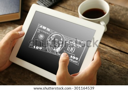 Money concept. Hands holding digital tablet with dollars image on it, close-up - stock photo