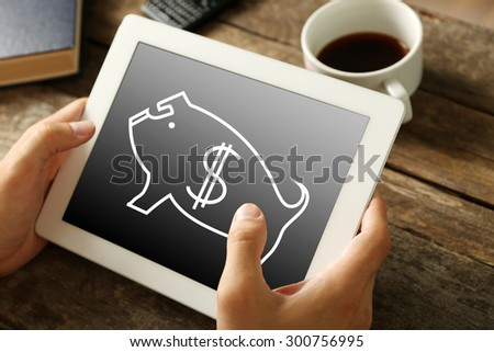 Money concept. Hands holding digital tablet with piggy bank image on it, close-up - stock photo