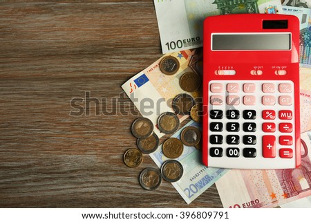 Money concept. Red calculator with banknotes and coins on wooden table - stock photo