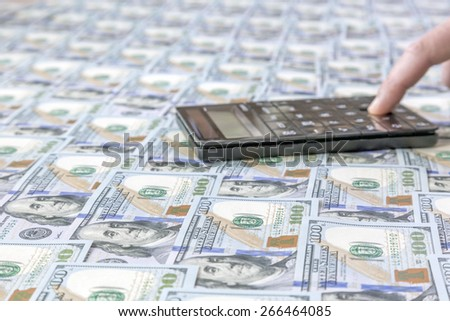 Money counting. The desk covered with US dollars hundreds new notes, calculator and human finger clicking the button - stock photo