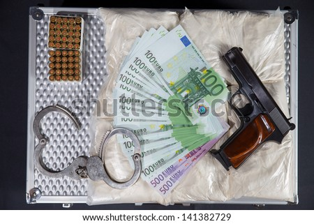 money, drugs, gun, handcuffs on suitcase - stock photo