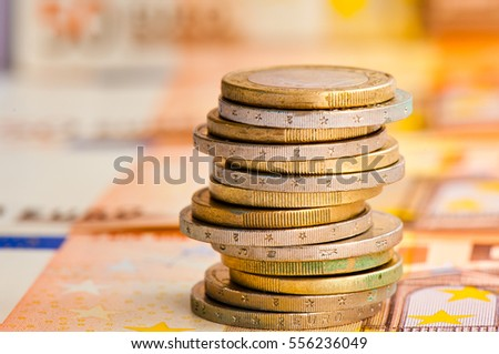 Money. Euro coins against euro banknotes background