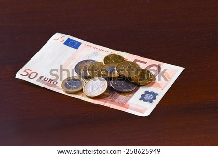 Money euro coins and bills close up isolated on wooden - stock photo