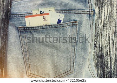 Money (euro) in a jeans pocket. Lens flare effect - stock photo