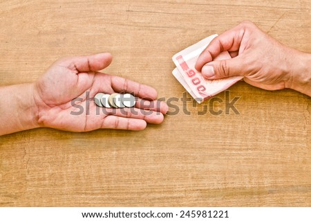 money exchange (hand giving coin to change with banknote in another hand) - stock photo