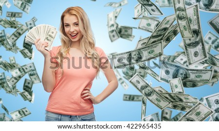 money, finances, investment, saving and people concept - happy young woman with dollar cash over money rain and blue background - stock photo