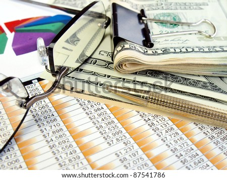 Money, glasses and pen on the table with financial data - stock photo