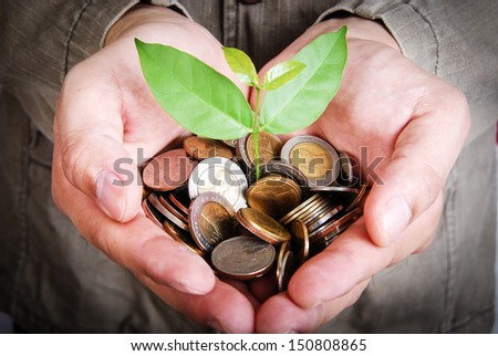 Money growing and saving with a man holding coins - stock photo