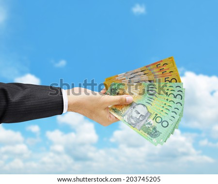 Money - hand holding Australian dollar (AUD) banknotes on blue sky background - stock photo