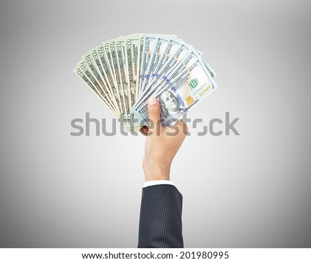 Money - hand holding United States dollar banknotes on gray background - stock photo