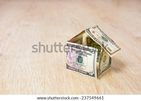 Money house made of dollar bills on wooden background - stock photo