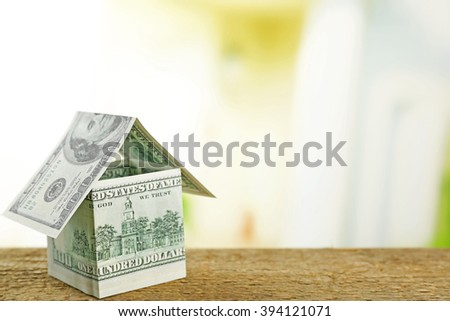Money house on wooden surface, close up - stock photo