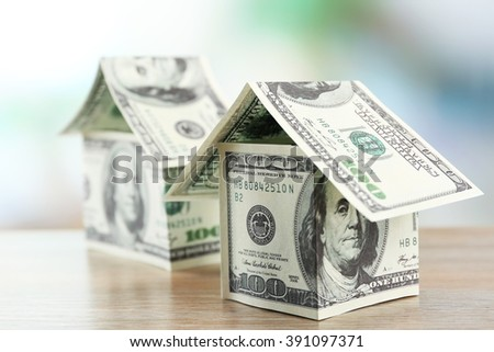 Money houses on wooden table, close up - stock photo